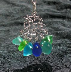 https://flic.kr/p/6USxdz | Sea Glass Jewelry - summer colors seaglass cluster necklace | This collection of teardrop shaped seaglass in all shades of bright blue and green took me years to gather! Colors are aqua, lime green, turquoise, cobalt blue, teal green and emerald green. Displayed from a sterling silver charm of interesting design. Who wouldn't envy you wearing it? Sold!