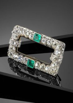 An Art Deco emerald and diamond plaque brooch by Cartier, of open rectangular form and pavé set with graduated cushion shaped diamonds in platinum and gold. Centred with two square shaped emeralds and with an internal border of black enamel. Signed Cartier Londres. 5cm wide. #Cartier #ArtDeco #brooch