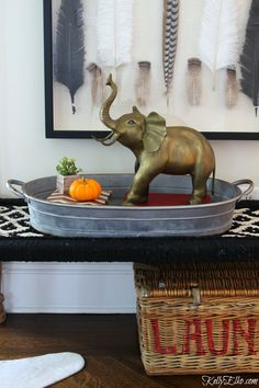 Brass is back! This vintage large brass elephant is a show stopper on a tray set on a woven black and white bench from World Market kellyelko.com sponsored