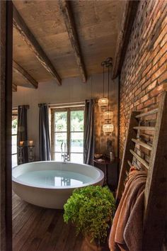 Modern vrij staand bad, oude stenen muur, houten balken en houten vloer