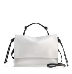 The Handheld in Off-White and Black from von Holzhausen featuring natural grained soft Italian leather with painted edges. Comes with removable crossbody strap, two open pockets on interior and removable signature wallet.