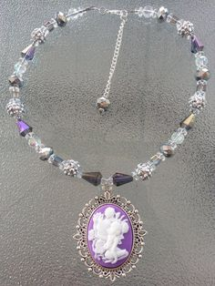 This is a 16 inch choker white and purple necklace. This can be made to any length. If you need a different length just message me. The necklace is made up of clear, purple and shiny silver beads and the white and purple fairly pendant.