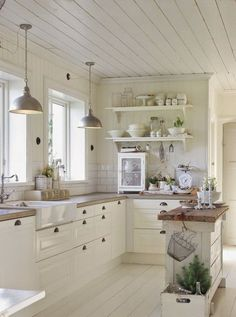 Farmhouse white kitchen with a rustic wood topped island. More via http://forcreativejuice.com/elegant-white-kitchen-interior-designs/