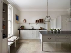 Black countertops take on a more homey, European feel when complemented by warm white walls, light floors, open shelving, and a not-too-substantial island