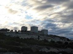 Cagliari- Castello dei Carroz- Il castello, situato in cima al colle omonimo, a quota di 120 metri sul livello del mare, sorge nel sito dove in epoca bizantina fu costruita la chiesa di San Michele; oggi è situato alla periferia nord della città di Cagliari e guarda la piana del Campidano. L'edificio ha forma quadrangolare con tre torri angolari raccordate da cortine murarie. È circondato da un fossato scavato nella roccia. Nel lato orientale si ergono due possenti torri quadrate con scarpe…