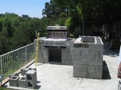 Outdoor Kitchen Construction using cinderblock.  Then add stacked stone veneer?  Thinking of trying this since prefabricated ones are $$$$$! (from Yardshare.com)