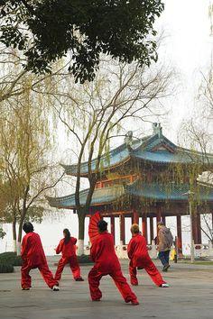 Women practising tai chi in front of a pavilion on West Lake, Hangzhou, Zhejiang Province, China, Asia