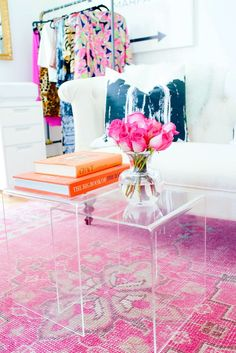 Lucite nesting tables as coffee tables, pink Persian rug, white sofa, orange books, and clothing rack