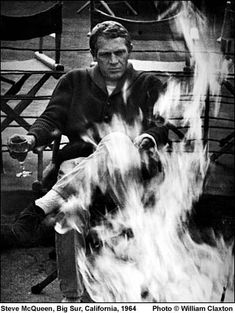 Steve McQueen enjoying a glass of wine by the fire