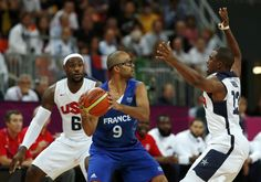 France's Tony Parker (C) is guarded by Lebron James (L) and Chris Paul of the U.S. during their men's Group A basketball match at the London 2012 Olympic Games in the Basketball arena  July 29, 2012.