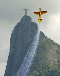 A stunt plane does its best impression of Christ the Redeemer.   30 Incredible Once In A Lifetime Shots