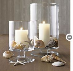 Summer table scape - sea shells in glass hurricanes with simple white candles.