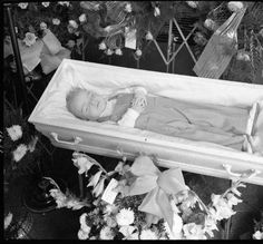 Neurath Funeral Home. Photo of casket & flowers of boy. An infant lies in a casket surrounded by flowers.            1948-08-24