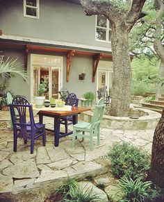 stone seating wall around tree connected to small flagstone seating area.