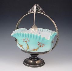 Victorian Art Glass Brides Basket, Simpson, Hall & Miller Stand. Unusual square shaped bowl with crimped rim. The bowl is the smoothest blue satin glass with white interior. Exterior hand enamel in a flowering branch and butterfly design, the interior painted with floral sprays.
