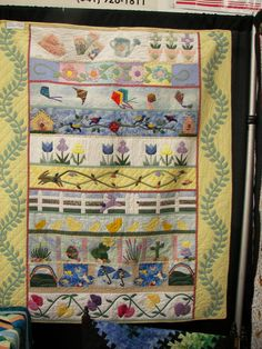 """""""Spring"""" row quilt.  Different in that there are different items in the row on a single theme. Particularly the kites. white picket fence"""