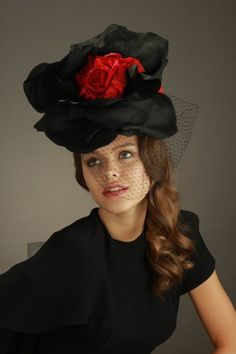 Yes, it's a flower! or two, or three: black silk petals, hand cut and mounted with ruby velvet blossoms. Trimmed with an insouciant veil.