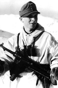A member of a ski-troop unit is posing for the photographer. Note the MP38 he is carrying, which features the old style retracting handle and the leather safety strap to fix the bolt in its forward position. Partly covered by the submachine gun are the magazine pouches, containing three magazines each.