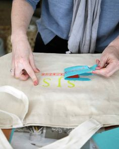 Stencil Strategy   Martha Stewart Living - To prevent her stencil from shifting, causing her to paint outside the lines, Janet Stein secured it to the tote with painter's tape. She then filled in the stencil using a paint-dipped foam pouncer.