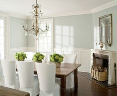 Elegant dining room with upper walls painted Benjamin Moore Wickham Gray over lower walls paneled in wainscoting with a traditional corner fireplace ...