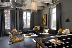 This glam loft living room is a modern take on the tradition color combination of black and gold.  The softer hues of these colors provide a fresh atheistic with a throw back to Mid-century modern accomplished through furniture and art selection.  By Kenneth Brown Design.