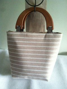 Soft tan and white stripe pocketbook. Great compliment to your summer vacation wardrobe. Find these and more on etsy/ SewReconstructed. com
