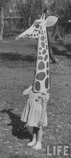 Allan Grant - A girl wearing a giraffe head toy by Charles Eames., June 1951