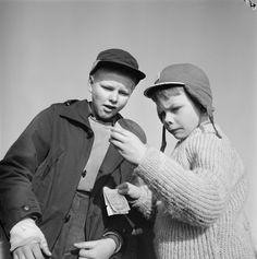 Kevään merkki: pikkupojat polttolaseineen. Kuvan pojat tarkkailevat mitä auringon lämpö saa aikaan. Helsinki 22.2.1961.   Valokuvaaja Eero Häyrinen.