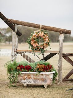 Tie props into the rustic wedding ceremony in unique ways, like fashioning a vintage bathtub as a large potted flower arrangement.