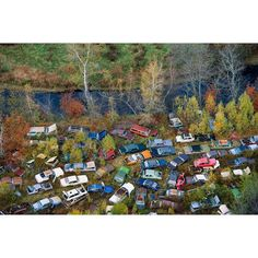 Junkyard Along River, NH. Image on display at the @decordovaspandm April 1- September 18 as part of the show Overgrowth. A subliminally disturbing image when considering the hazardous waste– crankcase and transmission oils, antifreeze, brake fluid, power steering fluid, battery acid– that will end up in the river. ©Alex MacLean