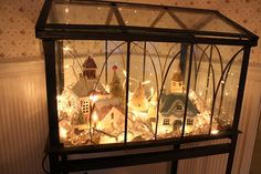 Cardboard houses inside a terrarium with lights