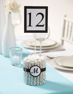 Michaels.com Wedding Department: Wilton® Candy Stick Table Number This clever candy centerpiece combines sweet style with tasty treats. Create a base of candy sticks and wrap with decorative ribbon and a monogram tag. Add your table number using a lollipop stick. Complete the look with Jordan Almonds and enjoy!