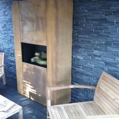 Design wood-burning outdoor fireplace and BBQ of weathering steel. Can be placed against à wall or free space.