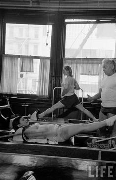 The Original Hundreds!   Joseph Pilate's teaches clients on the Reformer in his New York studio. Clients are doing The Hundred and Russian Splits.