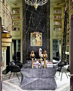 Library with a black marble accent wall, triangle-pattern rug, a cerused wood table, and an ornate gold deco banister