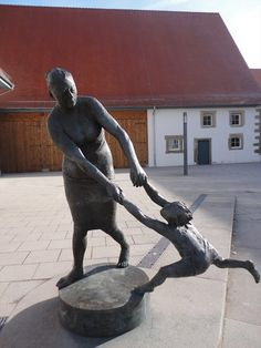 This is a statue of an old woman with a child which is located in front of the Zehnscheuer-Building in Bondorf, Germany, Baden-Württemberg.