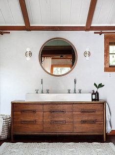 Shiplap on the ceiling and a repurposed vintage mid-century dresser as a bathroom sink vanity. Love!