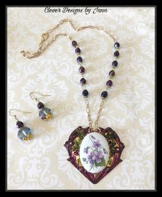 SOLD A beautiful heart is painted and a violet cab is attached to the center of the heart .. purple beads and gold plated chain complete this beauty .. matching earrings .. Clever Designs by Jann .. FOR SALE