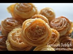 The Tunisian Deblah | Arabianmama - video - make a pastry, roll out thin, spin around a fork while in hot oil, then cook and drizzle with syrup