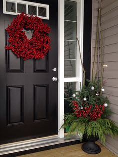 Red wreath would work on our green door.  Like the urn arrangement too with tall twigs for height.