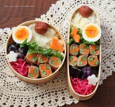Bento box featuring carrot & green bean meat rolls, marinated purple cabbage, hard boiled egg, fried eggplant, and rice with umeboshi