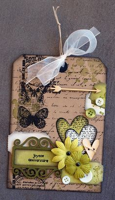 Brown tag stamped with script. Green hearts and embellishments. Tags cut a only half stuck on. Butterflies arrows flowers. And tag frame.