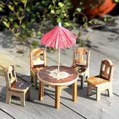 Wooden Desk, Chair and Umbrella Set. www.teeliesfairygarden.com . . . Fairies love getting together with their friends. This tiny set is a great place for them to get together and enjoy fairy cocktails – one of their favorites is a blend of fruits picked from their own trees. #fairyfurniture