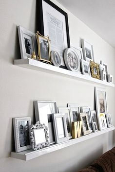 Neat floating wall shelves full of pictures of different sizes, shapes and colours... yet it works so well.