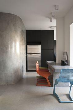 As cadeiras da Miniloft acenderam o projeto neutro do designer de interiores Francisco Cálio. Repare que elas são o toque perfeito de cor para a base sóbria, com armários pretos e piso e paredes de cimento queimado