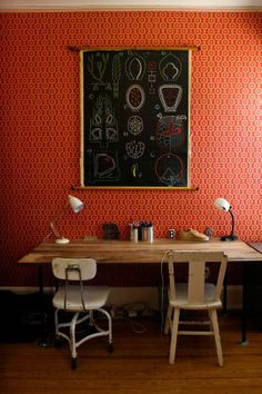 Warm-toned office space: Great contrast of red abstract wallpaper and black chalkboard!