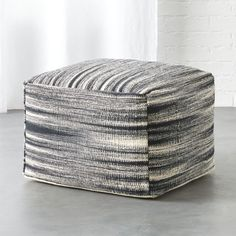 Shop nelio pouf.   Woven cotton blend squares up a traditional ikat vibe in black and natural.  Casual versatile shape pulls up as an ottoman or holds its own as a stool.