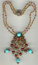 Necklace from the 1930s that reflects a Southwest flavor. Apprently Haskell visited this area & produced a number of pieces with these colors.  Necklace has two strands of silver-tone chain accented with turquoise and cranberry glass beads. The central element consists of turquoise art glass beads, cranberry glass beads in several sizes, small tuquoise glass flowers all mounted on an elaborate silver-tone metal floral background. Note the elaborate slide clasp. Unsigned Haskell.