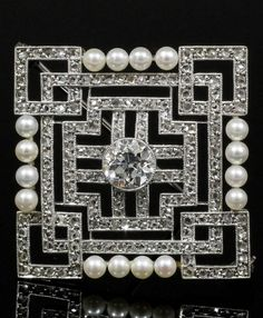 An Art Deco platinum, diamond and pearl brooch, 1920s. The square brooch of geometric design, the centre set with an old cut diamond of approximately 1ct, contained within fine borders channel set with 180 rose cut diamonds, bordered to either side by four small pearls, mounted in platinum, 3.2 x 3.2cm. #ArtDeco #brooch