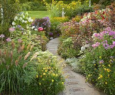 Wonderfully colorful cottage garden bordering this path made of concrete, but with bricks inlaid at intervals - BHG